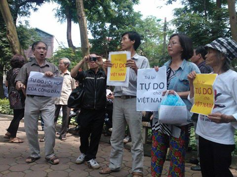 """Vietnamese hold up signs that say, """"Give Vietnam back its Freedom."""""""