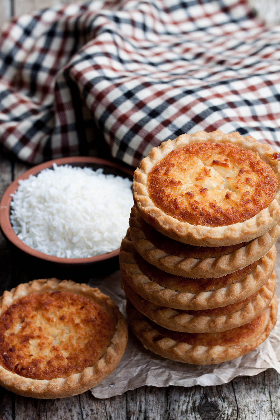 Stack of coconut tarts on wooden table