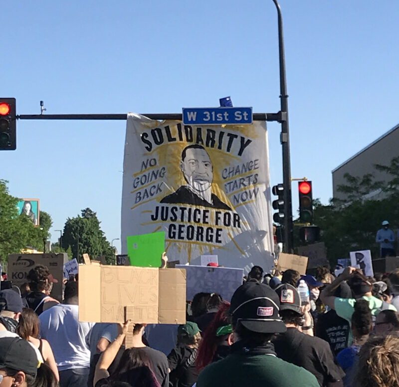 """Protestors marching down a street in Minneapolis. A banner hangs off the sign post for W 31st St. The banner shows a drawing of George Floyd and reads """"Solidarity,"""" """"Justice for George,"""" """"No Going Back,"""" and """"Change Starts Now."""""""