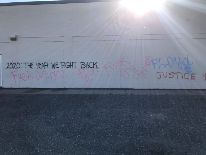 """Graffiti on the side of a white building that reads """"2020: The Year We Fight Back,"""" """"Fuck America,"""" """"Fuck [heart emjoi],"""" """"Fuck the thruth,"""" """"Floyd,"""" and """"Justice"""""""