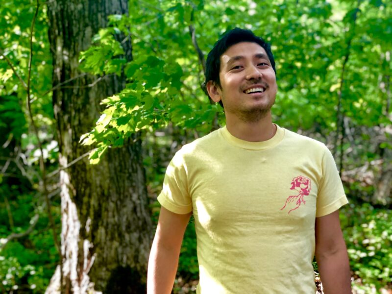 A photo of the author, Khoi Nguyen, wearing a yellow t-shirt while standing in the woods.